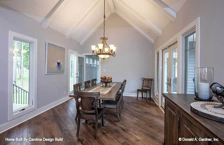 This dining room has a dark rustic hardwood flooring that pairs well with the dark rectangular wooden dining table paired with wooden chairs and topped with a chandelier.