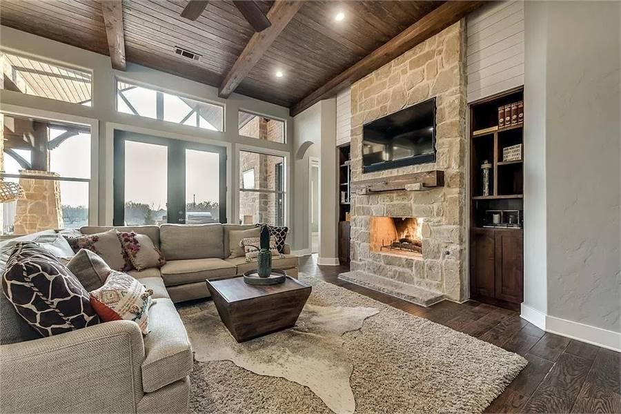 Craftsman living room with wood-beamed ceiling, dark hardwood flooring, and a stone fireplace lined with a rustic mantel. A wall of windows bathes the room with natural light.