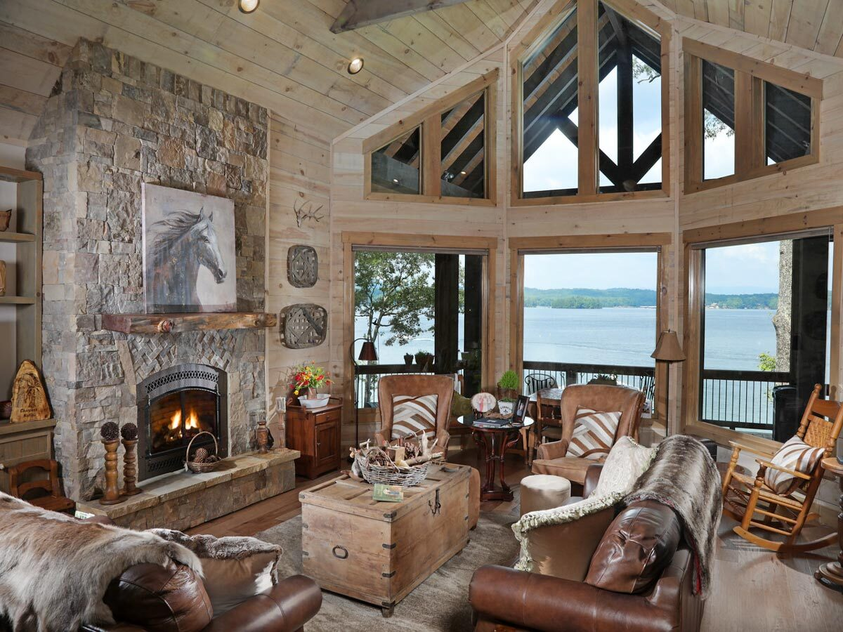 This living room has brown leather seats, a stone fireplace, and a trunk chest coffee table that matches the wood-paneled walls. Massive windows at the right side take in incredible views.