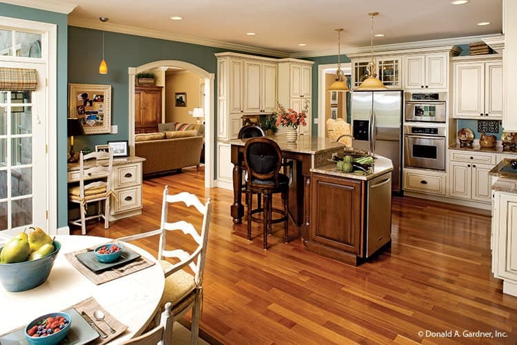 This is an eat-in kitchen with a hardwood flooring to match the brown wooden kitchen island and its stools contrasted by the bright beige cabinetry and stainless steel appliances.