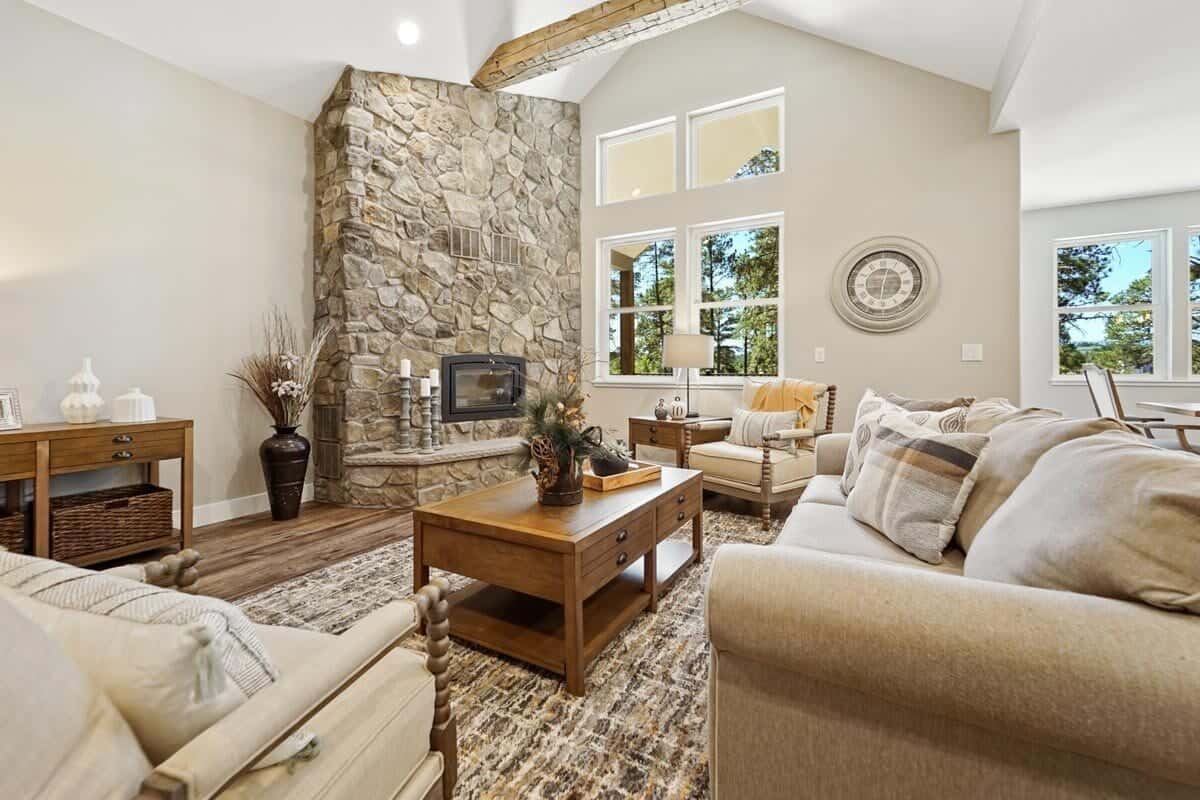 A corner fireplace clad in striking stones creates a stunning character to this beige living room. It is furnished with fabric seats, wooden tables, and a large area rug.