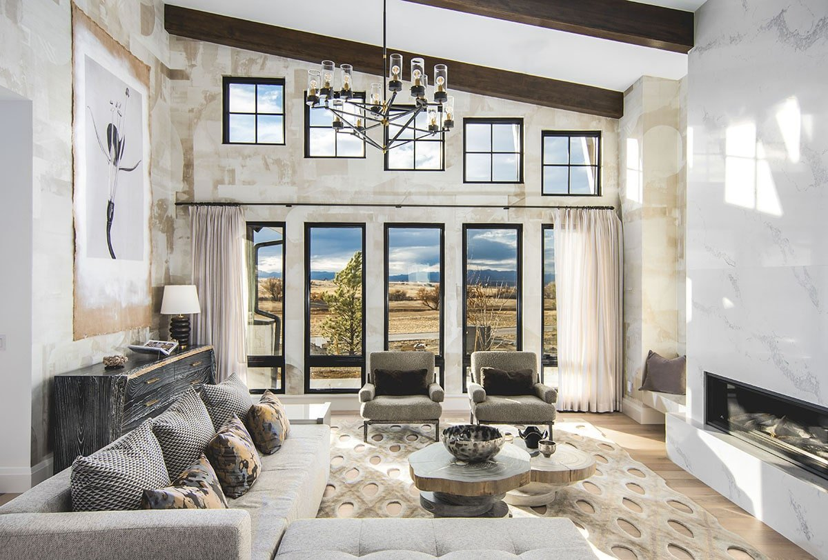 This craftsman living room features a wall of windows and a shed ceiling lined with natural wood beams. Tall marble fireplace and a unique area rug topped with a modular coffee table add nice touches.