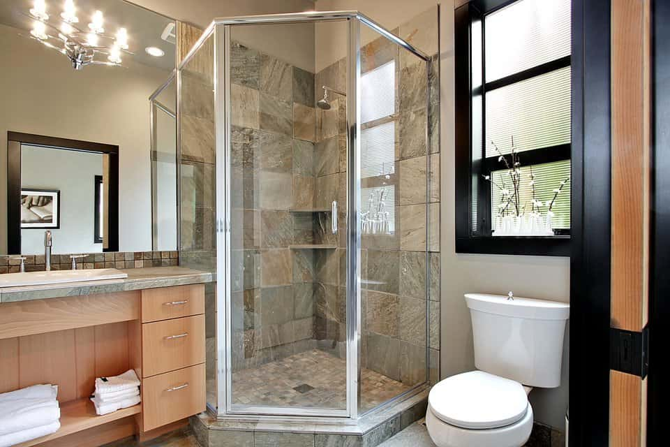 This charming bathroom has a glass-enclosed shower area placed at the corner in between the toilet under the window and the wooden vanity topped with a large mirror.