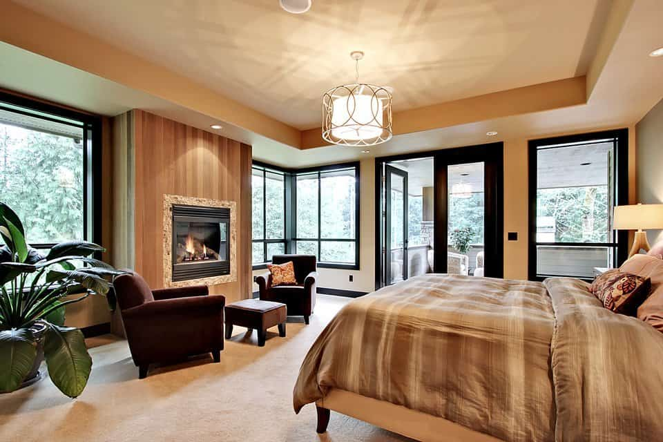 This is spacious primary bedroom with a large beige tray ceiling hanging a semi-flush mount lighting by the foot of the bed that has a sitting area. This is warmed by the fireplace and illuminated by the surrounding glass doors and windows.