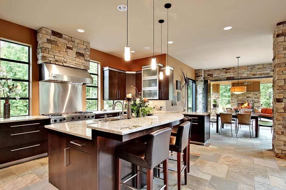This kitchen has a large dark brown kitchen island with a built-in second tier counter for the breakfast bar that is paired with uoholstered stools and topped with warm yellow pendant lights.