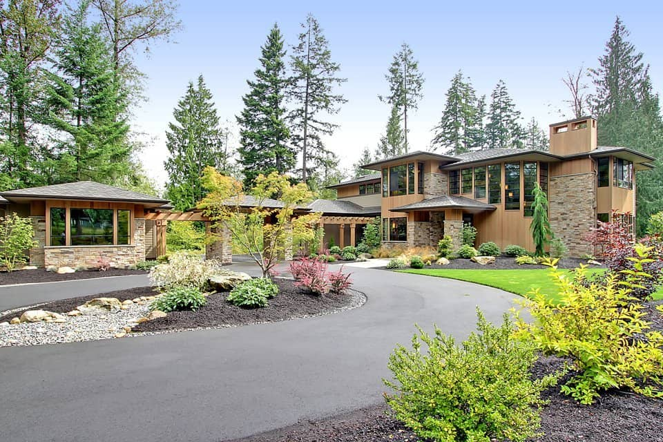 This is the front of the house with a wide asphalt driveway augmented by the various colorful shrubs and grass lawns along with tall pine trees.