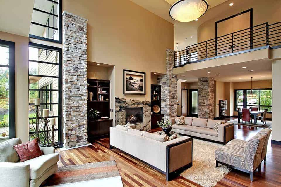 The beige walls of this spacious living room are adorned with large stone pillars that match the stone mantle of the fireplace across from the beige sofa set. These are the topped with an indoor balcony with black metal railings.