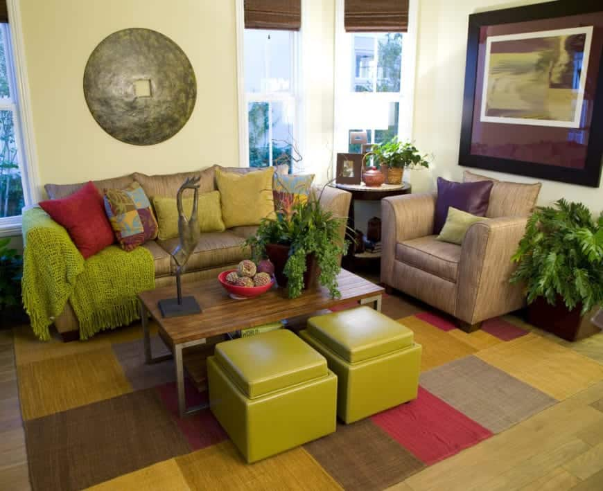 Green living room designed with wall arts and a colorful rug over hardwood flooring. It has a fabric sectional and chair filled with multi-colored pillows and green throw blanket.