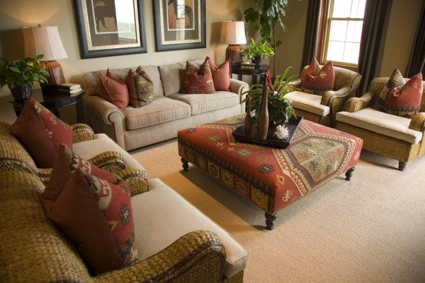 This living room is filled with a beige couch and rattan chairs fitted with beige cushions and red printed pillows that complement with the ottoman.