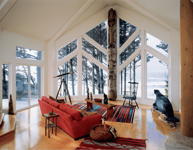 Gorgeous living room surrounded with glass windows overlooking a magnificent ocean view. It has a cathedral ceiling and polished hardwood flooring topped with colorful rugs.