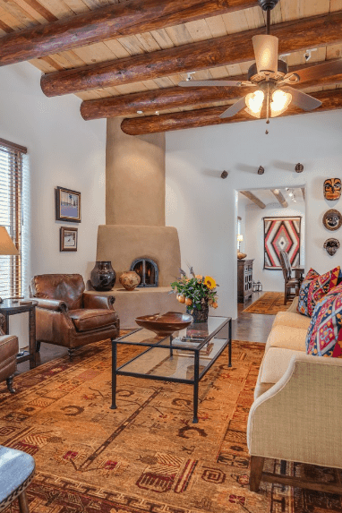 A ceiling fan with lamps that hung from a wood beam ceiling illuminates this southwestern living room. It has a glass coffee table topped with decors and sits on a brown printed rug.