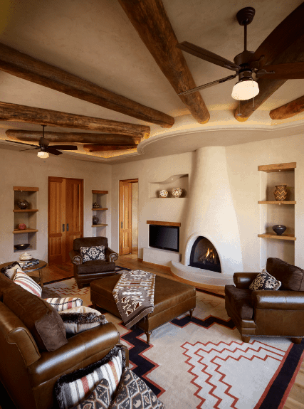 Cozy living room features a kiva fireplace accented with round wood beams. It faces the brown leather sofa set filled with patterned and striped pillows.