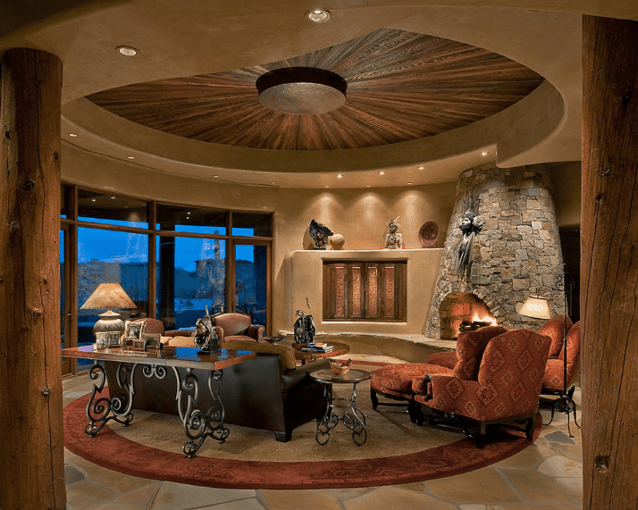 The elegant round living room showcases a sunburst ceiling design fitted with recessed lighting. It includes a stone fireplace and flooring topped with a round velvet rug.