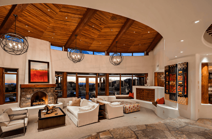 The expansive living room offers two sitting areas lighted by spherical chandeliers and recessed lights mounted on the wood beam ceiling.
