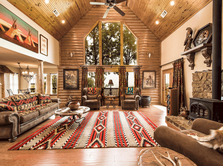 Warm living room showcases a high cathedral ceiling and glass windows covered with patterned draperies that complement with the area rug and pillows laying on a brown sectional.