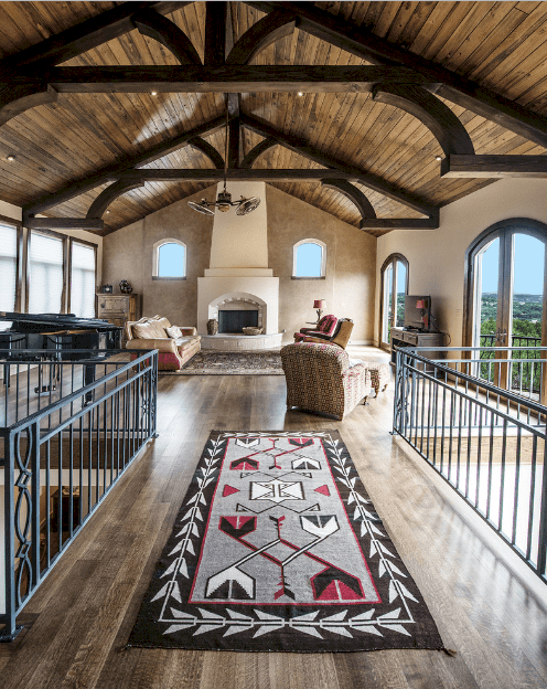 This living room features a bridge framed with wrought iron railings and topped with a black patterned rug over dark hardwood flooring. It has arched windows and wood plank cathedral ceiling.