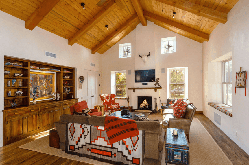 Bright living room boasts a wood cathedral ceiling and hardwood flooring. It has glass windows with built-in seat nooks accented with striped cushions.