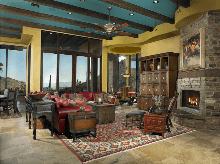 Southwestern living room showcases a green ceiling lined with dark wood beams and yellow walls fixed with a stone brick fireplace below a lovely framed painting.