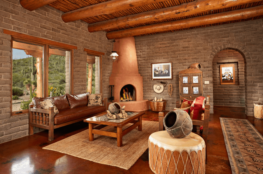 Warm living room surrounded with brick walls that are fitted with wooden framed glass windows and an archway. It includes a kiva fireplace and wooden sofa set over red stained concrete flooring.