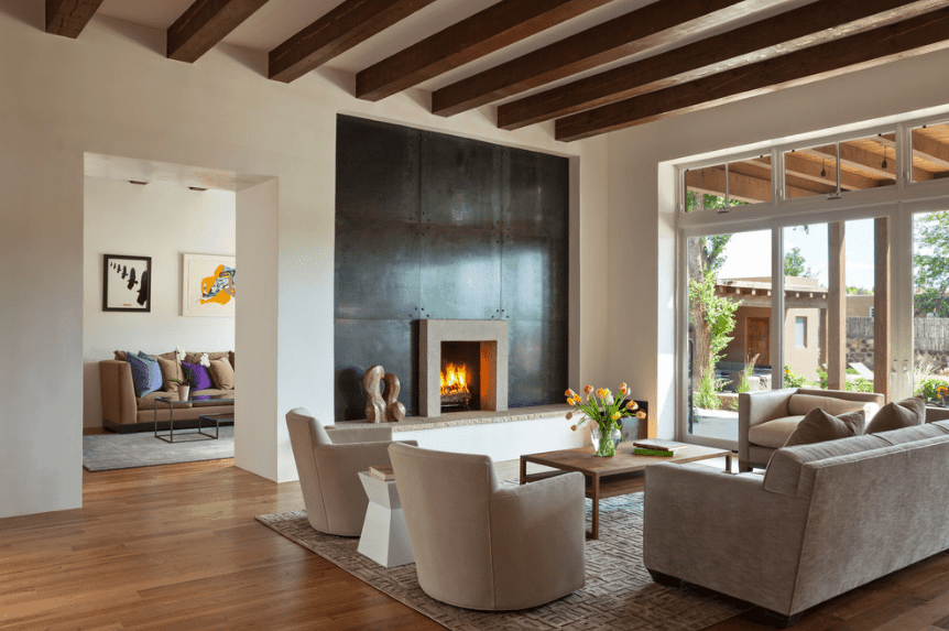 The sleek living room features a black paneled accent wall fixed with a fireplace. It faces the wooden coffee table surrounded with a gray sofa and beige armchairs.