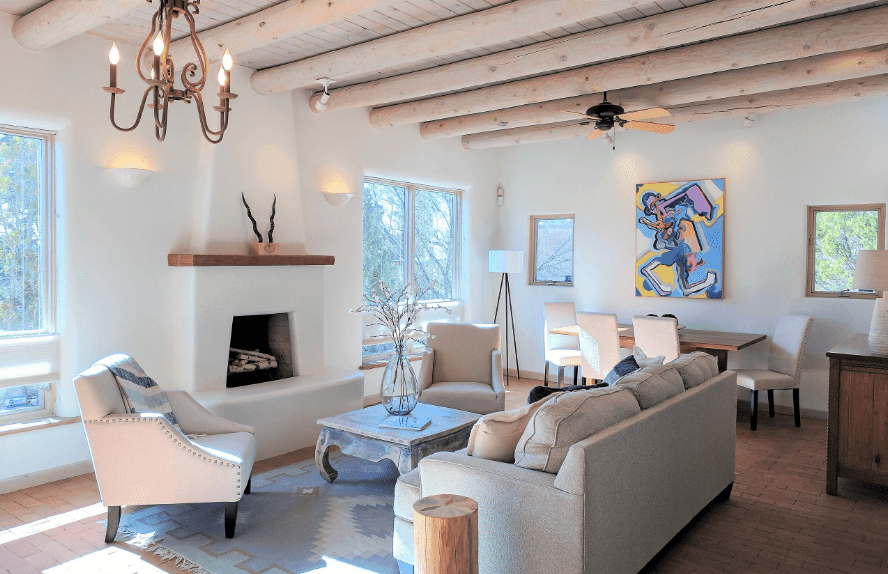 A vintage chandelier that hung from the wood beam ceiling illuminates this white living room along with natural light that streams through the glass windows.