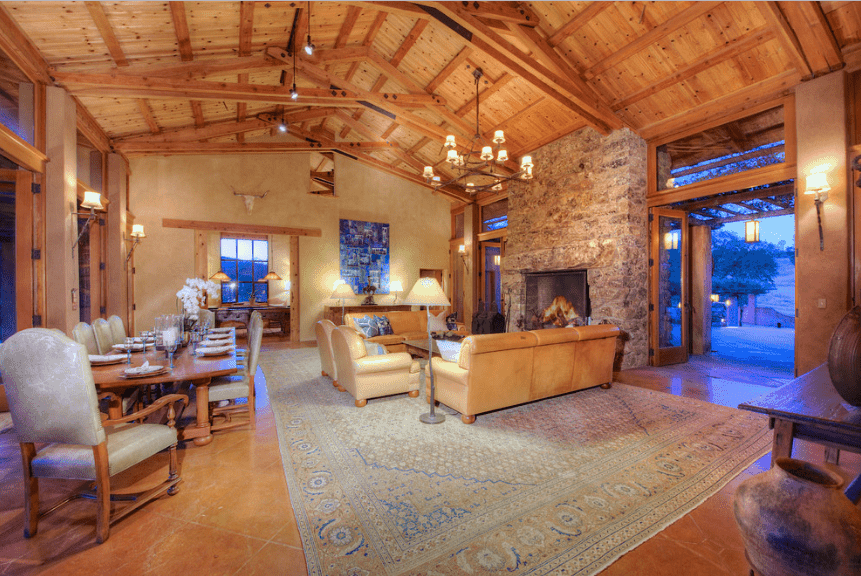 An open living room with wood plank cathedral ceiling and a stone accent wall fitted with a fireplace. It also has a terracotta flooring topped with a vintage rug.