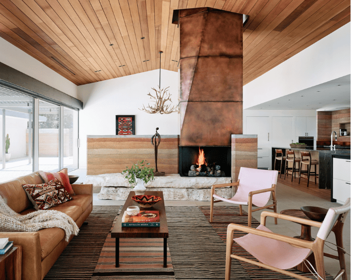 An antler chandelier hangs beside a rustic chimney in this living room. It has a wooden coffee table surrounded by a leather sofa and light pink chairs.