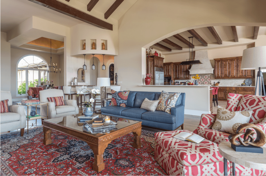 Southwestern living room features a blue sectional paired with white armchairs and a red patterned recliner with ottoman. It includes a wooden glass top coffee table that sits on a vintage rug.