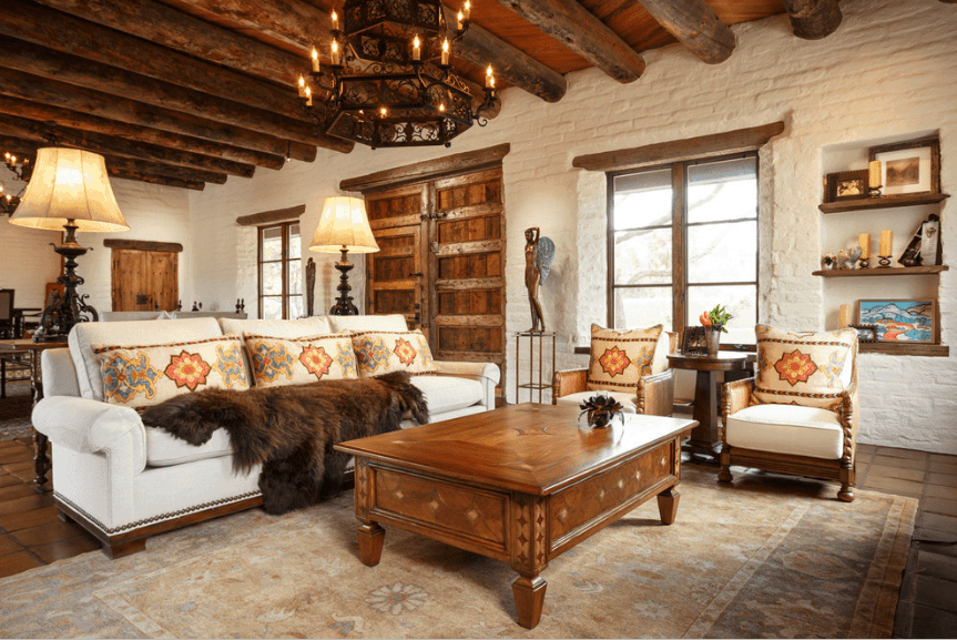 Cozy living room with white brick walls and wood beam ceiling with a hanging vintage chandelier. It has a white sofa filled with floral pillows and a brown faux fur blanket with matching chairs and wooden coffee table.