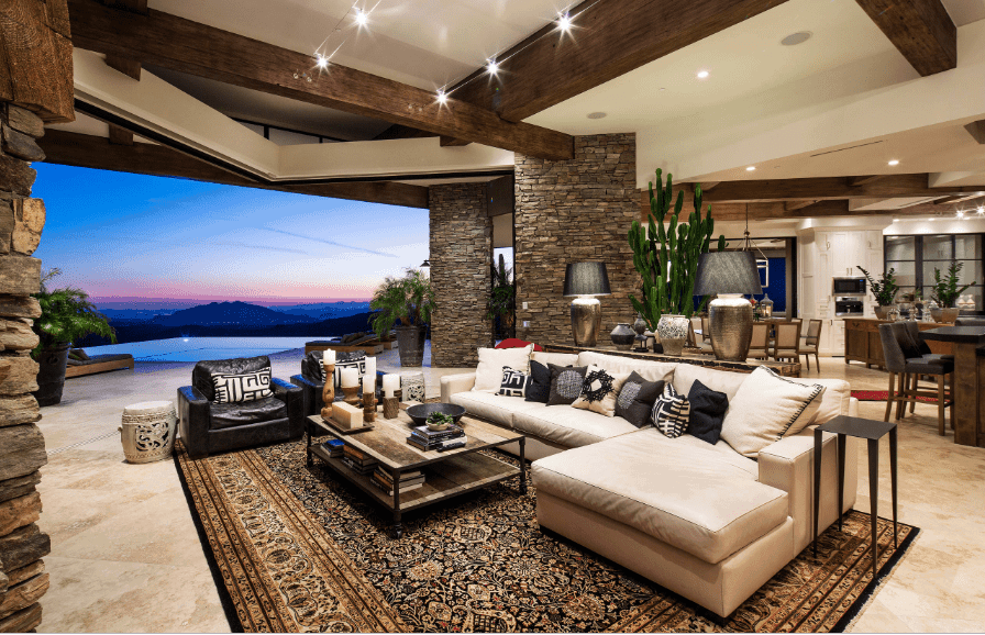 The luxurious living room showcases stone brick pillars and a panoramic window overlooking a stunning mountain view. It includes a marble flooring topped with a classy black rug.