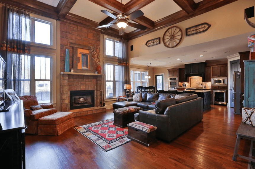 An open living room boasts a hardwood flooring and a coffered ceiling with a hanging ceiling fan. It has a brick fireplace with wood mantel decorated with artwork and vases.