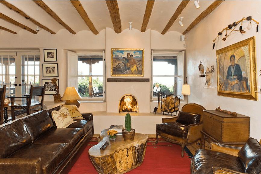 This living room features a barrel vaulted ceiling lined with natural wood beams. It includes a leather sectional and tree stump coffee table sitting on a red area rug.