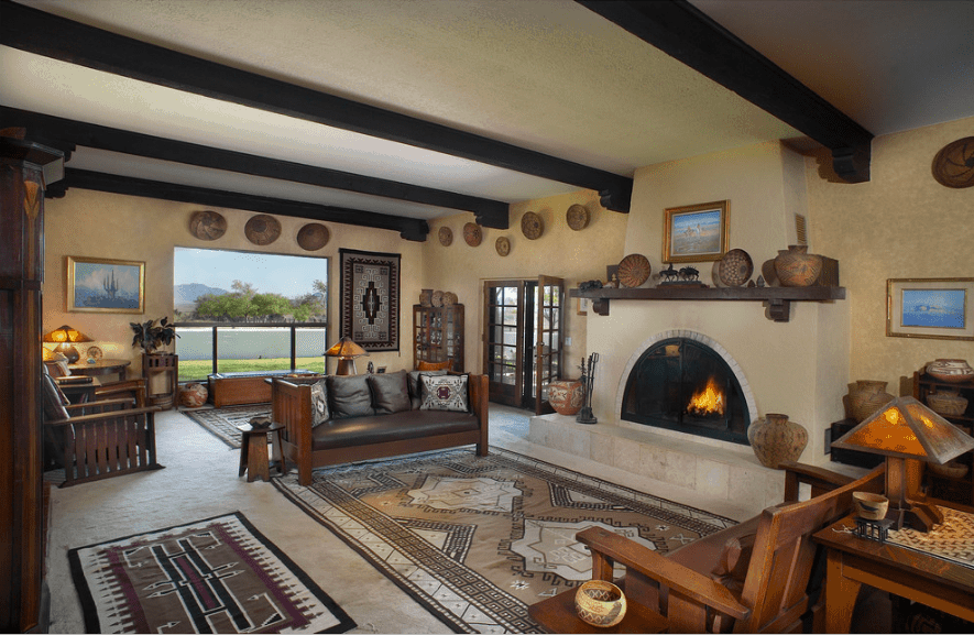 Southwestern living room showcases a fireplace fixed to the cream wall filled with artworks and round wooden decors.