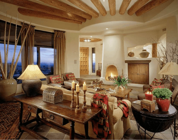 Magnificent living room offers a kiva fireplace accented with round wood beams attached to the white ceiling. It has diamond patterned flooring topped with vintage rugs.