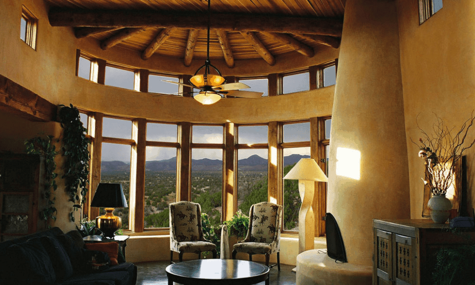 Living room surrounded with glass windows overlooking a serene mountain view. It has a ceiling fan that hung over a pair of highback chairs and a round coffee table.