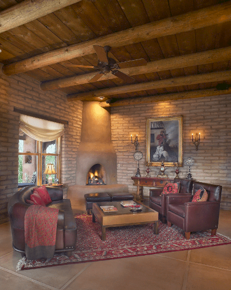 Southwestern living room showcases a framed wall art mounted on the brick wall. It has a wood beam ceiling and tiled flooring topped with a red vintage rug.
