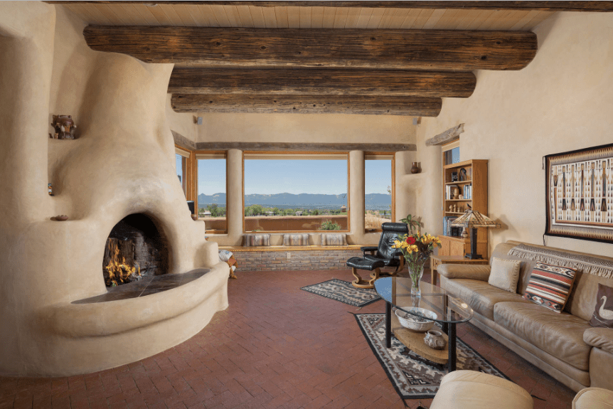 Magnificent living room boasts a kiva fireplace and glass windows with a panoramic view of the mountain. It also has a window seat nook clad in stone bricks and topped with pillows.