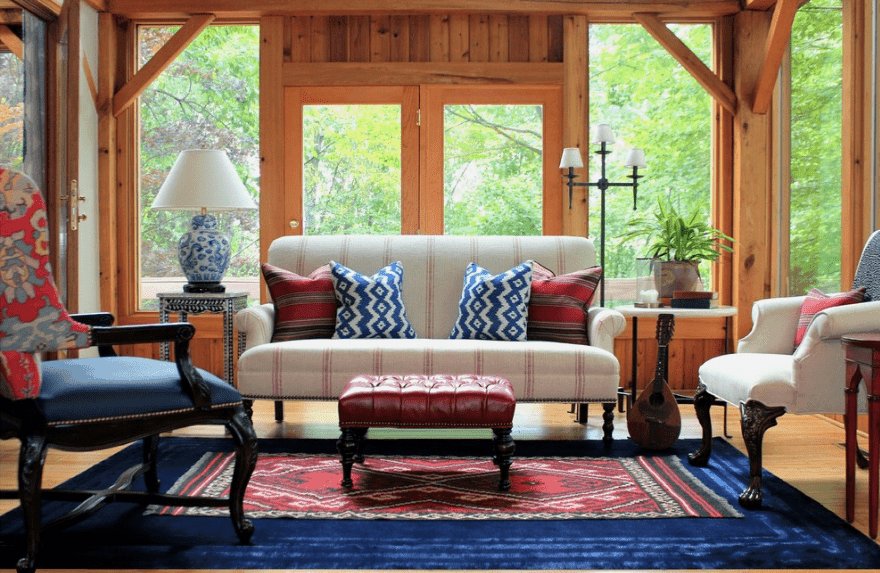 Fresh living room enclosed with wood paneled glazing. It has hardwood flooring topped with a lovely blue and red area rug.