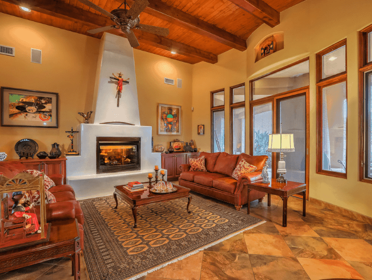 Red fleur-de-lis patterned pillows lay on the brown leather sectionals in this mustard yellow living room. It has diamond flooring and wood beam ceiling.
