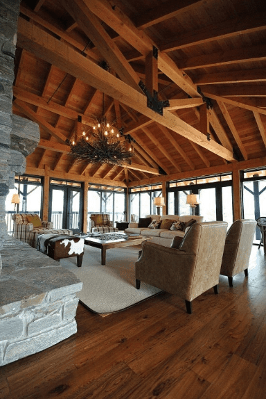 Rustic living room surrounded by full height glass windows allowing plenty of natural light in. It is illuminated by a twig chandelier that hung from the wood beam ceiling.