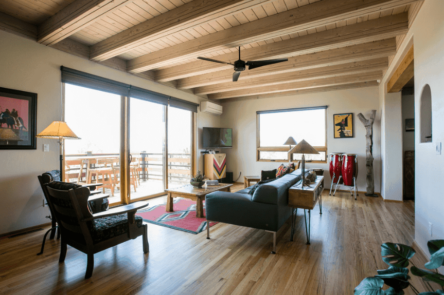 Bright living room features glass doors that open to the balcony. It has light hardwood flooring that complements with the wood plank ceiling.