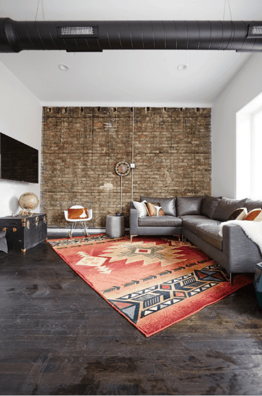 Southwestern living room showcases a stone brick accent wall and rustic wood plank flooring. It has a gray L-shaped sectional that sits on a red printed rug.