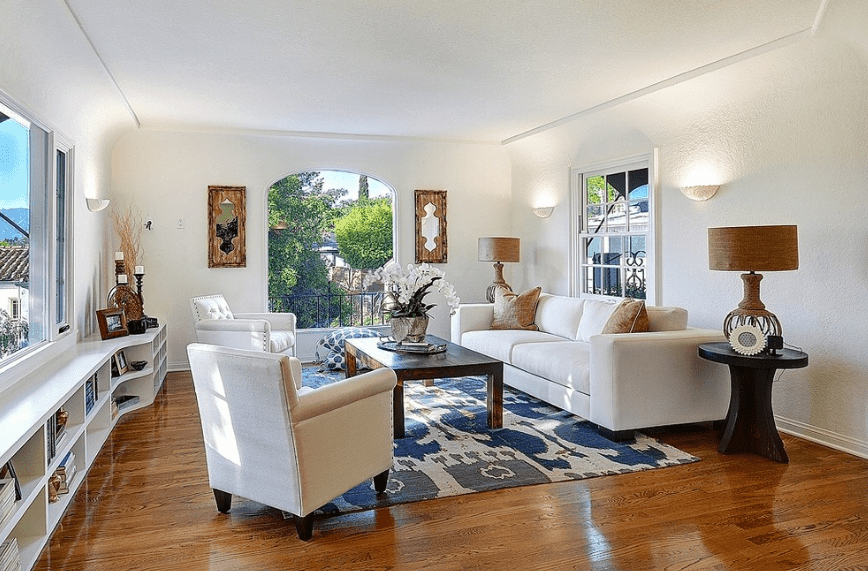 Clean white living room boasts a polished hardwood flooring topped with a lovely blue rug. It is lighted by wall sconces and rattan desk lamps that sit on round wooden side tables.