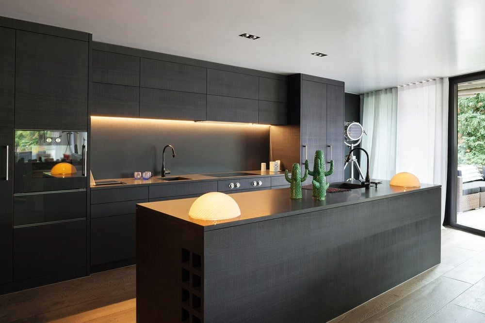 This gorgeous and modern Southwestern-style kitchen has pitch black modern cabinetry on its peninsula and its kitchen island that is adorned with a couple of dome table-top lighting as well as three ceramic cacti that stands out against the pitch black countertop.