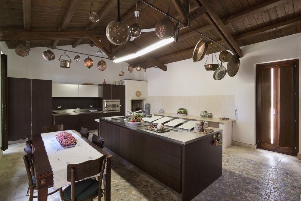 This spacious kitchen has enough space for a large black wooden kitchen island and a large dark wooden dining set in the middle of its mosaic stone flooring. The kitchen island and dining table matches with the peninsula and the cathedral ceiling that has exposed beams decorated with used pans and pots.