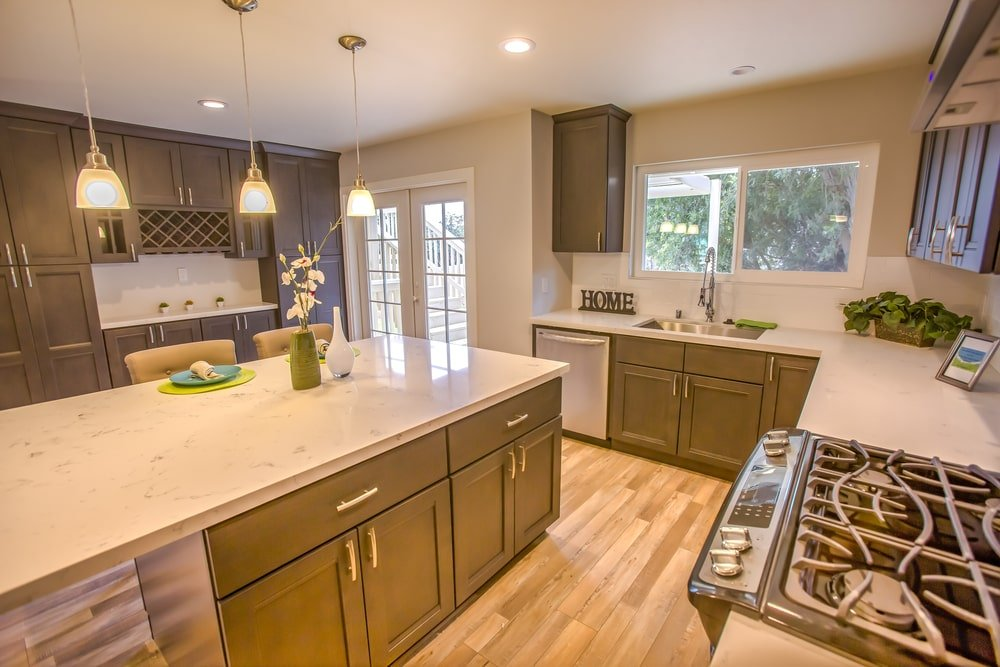 This simple Southwestern-style kitchen has simple avocado-colored shaker cabinets and drawers that has a classic look to its pairing with hardwood flooring and white marble countertops illuminated by the three small pendant lights over the kitchen island.
