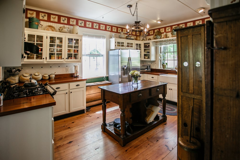 This is a homey Southwestern-style kitchen with a white ceiling that hangs a small wrought iron chandelier over the wooden table serving as a small kitchen island. This ceiling is lined with small images of chickens on the uppermost layer of the walls that is almost filled with cabinets and decors.