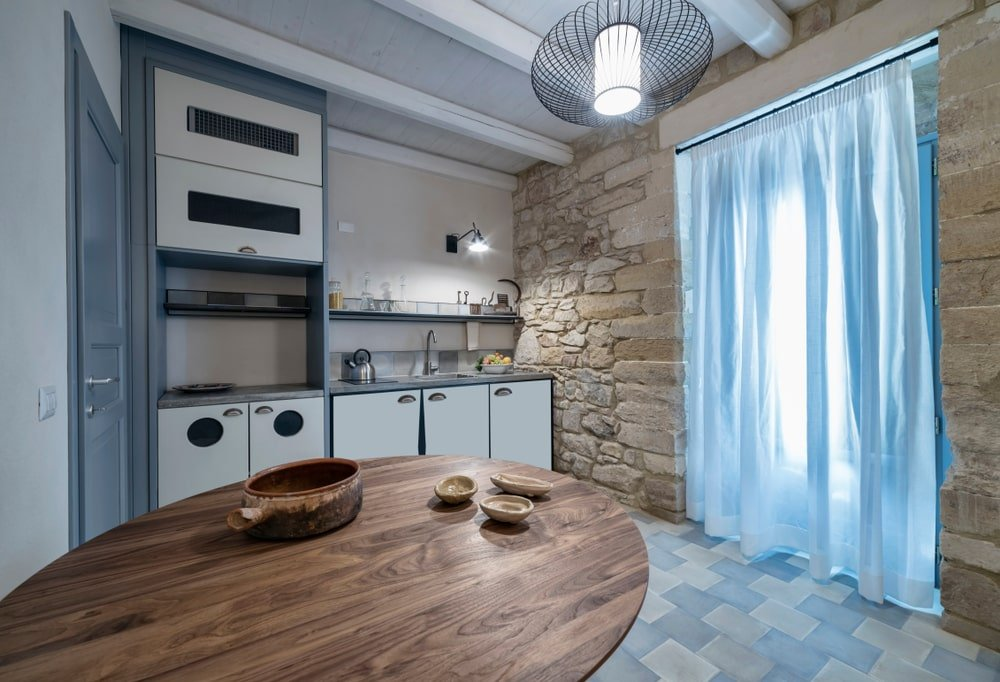 This is a simple Southwestern-style kitchen with a beautiful rough textured rock wall that supports the large curtained entryway to this kitchen. This textured wall is contrasted by the modern white and gray small kitchen peninsula that goes well with the white wooden ceiling and brick flooring.