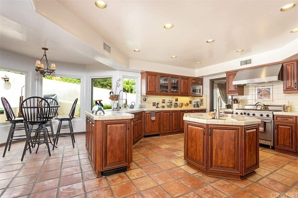 The charming terracotta flooring tiles of this Southwestern-style kitchen is a perfect match for the classic wooden cabinets of the small kitchen island and the surrounding U-shaped kitchen peninsula that follows the lay of the white tray ceiling.