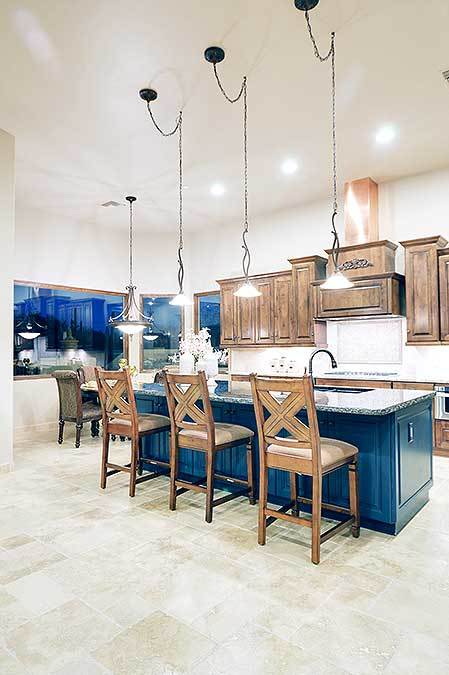 The bright blue wooden kitchen island stands out in this Southwestern-style kitchen with a light marble flooring complemented by wooden chairs on the breakfast bar illuminated by the brilliant pendant lights. This also illuminates the wooden shaker cabinetry of the peninsula.